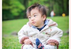 公園の芝生の上に座る男の子