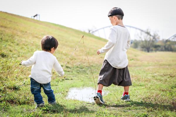 雨上がりの水たまりで遊ぶ兄弟 後ろ姿