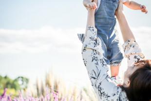 西日の当たるお花畑でママに高い高いをされる女の子