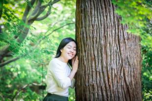 女性プロフィール写真 森の中で大木と一緒に