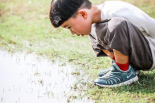 水たまりを見つめる少年