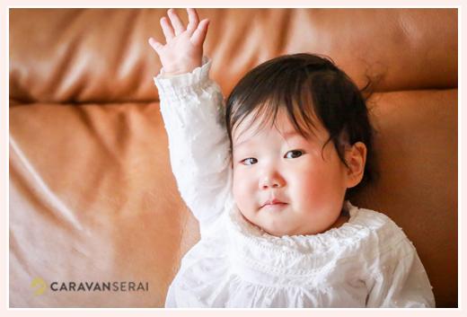 はーいと手を挙げる1歳の女の子