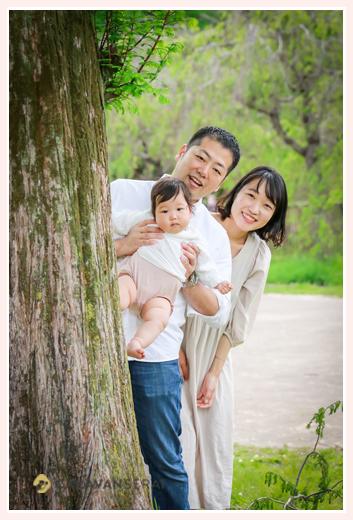 公園で家族写真 木の陰から顔を出す親子